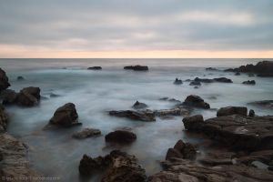Rocky and cloudy beach by isotophoto