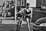 Young lady cyclist crossing the road by Vincent-Malcolm