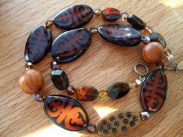 black and orange tribal necklace by merpagigglesnort