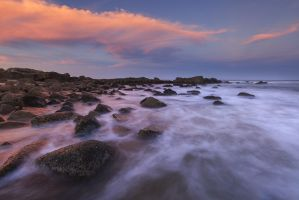 Pink and Blue and a beach with some Rocks by carlosthe