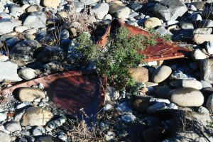 Rusted Metal Buried in the Rocks along the River by RayMackenzie