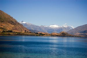 NZ Deep blue river, to snowcapped mountains by Chunga-Stock